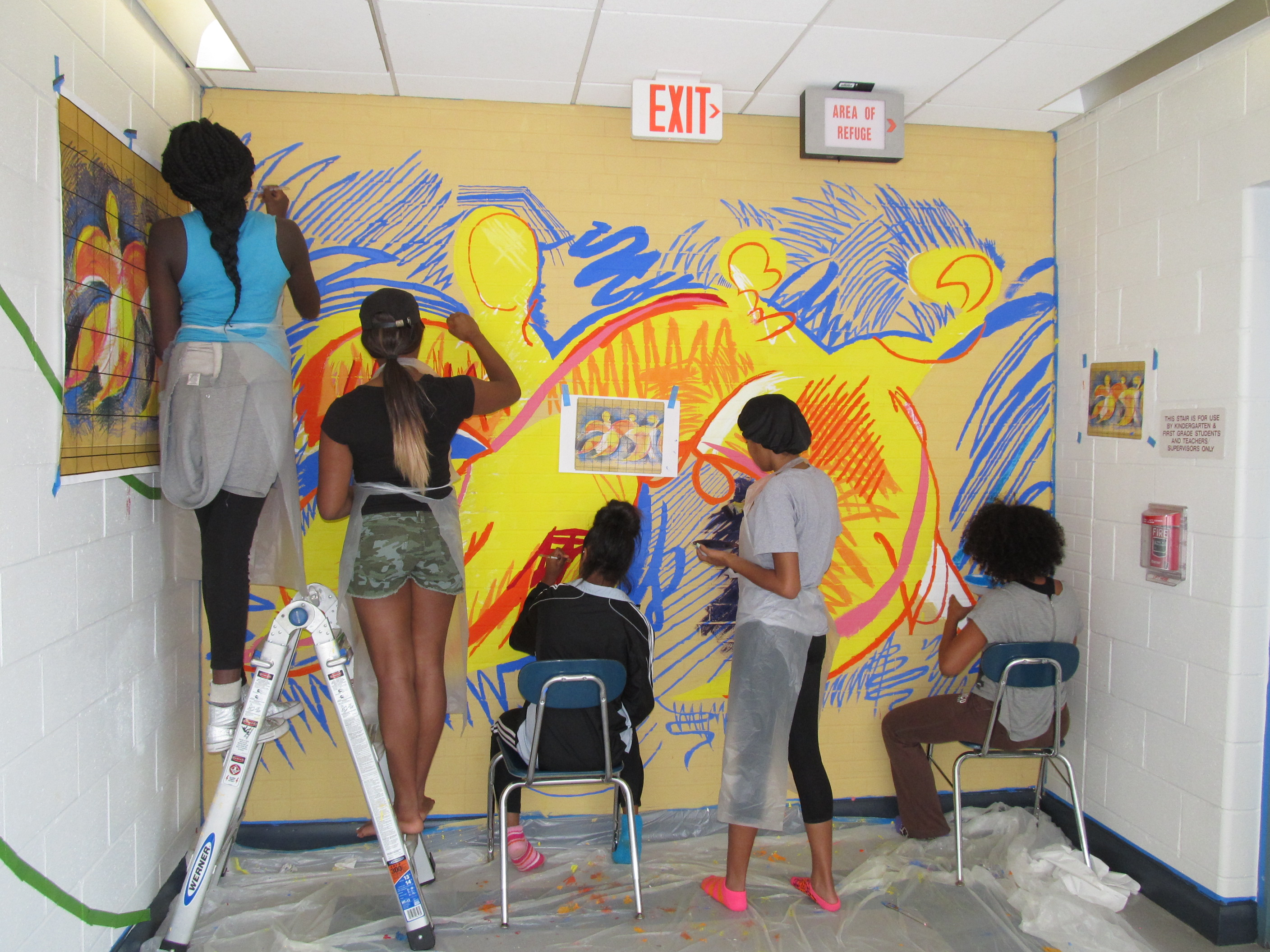 Students painting bright mural in a hallway