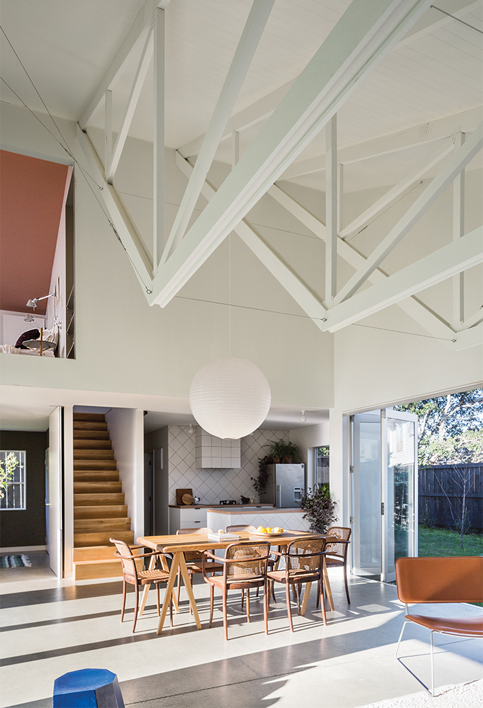 New Zealand great room with exposed trusses, paper lamp, and dining table