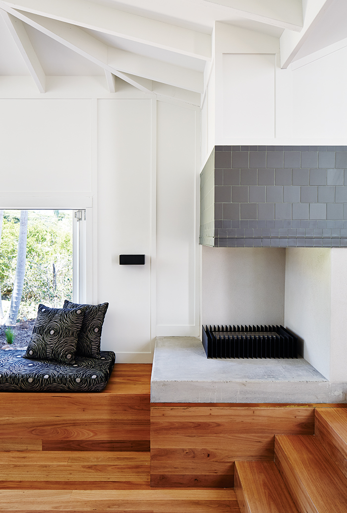 Modern timber house living area fireplace covered by charcoal tiles and a custom bench