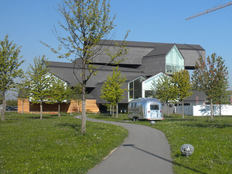"""The newest completed building on campus is the VitraHaus, designed by Basel-based firm <a href=""""http://www.herzogdemeuron.com/index.html"""">Herzog & de Meuron</a> in 2010. The structure features seven balancing longhouses, and its design took the world by s"""