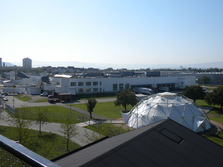 """The uppermost longhouse of the VitraHaus opens onto a balcony. This view overlooks Gehry's factory and <a href=""""http://www.dwell.com/people/buckmister-fuller.html"""">Buckminster Fuller's</a> Dome."""