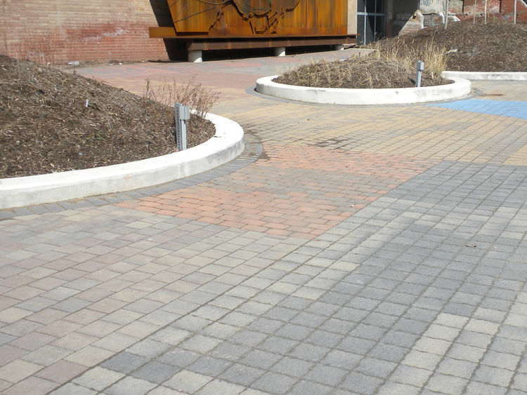 The paved entrance to the site features bricks made when the Brick Works was a functioning brickyard and highlights the variety in color and type that were produced.