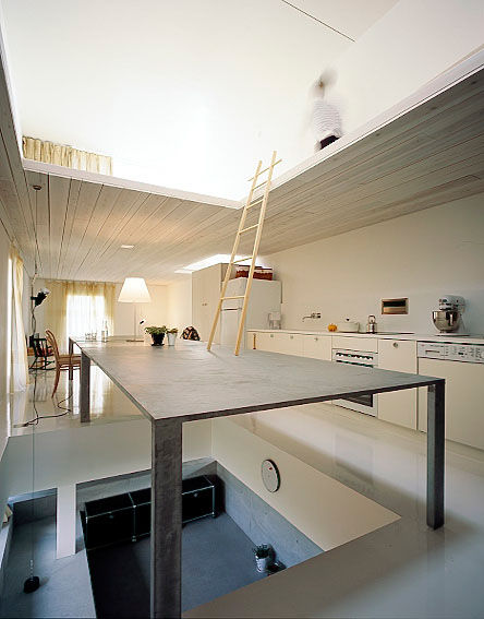 This image best illustrates the ambiguous spatial relationships in the home. The black slab acts as a mezzanine as well as a place to eat and gather.