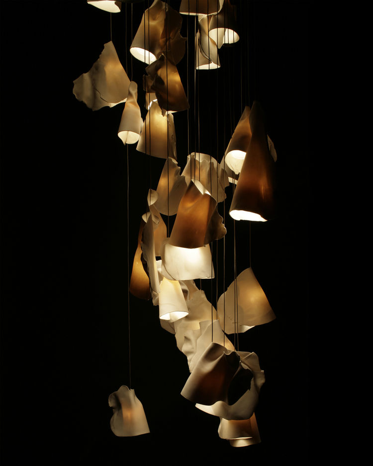 Arbel: The 21 was inspired by the sporadic and often discordant arrangements that barnacles form on a rock surface.  Each pendant is made of thin sheets of raw white porcelain wrapped around frosted blown borosilicate glass cones of varying sizes. The res