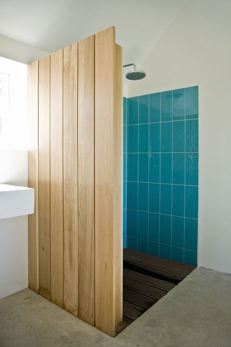 """Colored tiles in the shower are revealed behind a cedar wood wall. """"The sound of falling water on wood and the surrounding fields form the background,"""" say the architects. """"This was our way of introducing an immaterial idea of what luxury actually could b"""