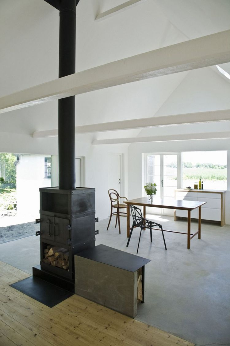 The two-sided stove is installed in the heart of the house, elevated slightly to bring the fire closer to eye-level. The stove marks the meeting of the new concrete floor with the old wooden floor. Photo by Laura Stamer.