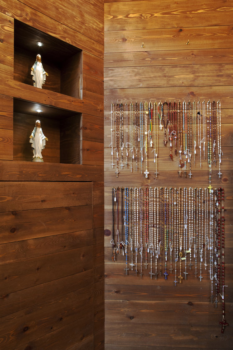 The shop is small in size, about 350 square feet, and a tacit elegance runs throughout. Simple recesses in the wall become display cases for religious icons and rosaries hang from minimalist pegs. Very little has been done to the surface of the wooden wal