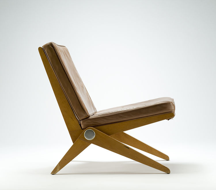 "A 1949 lounge chair in birch and leather by Pierre Jeanneret, a Swiss architect who moved to Paris in 1920 and worked in the office of his cousin Charles Édouard Jeanneret, aka Le Corbusier. First called the ""92 chair"" and featured in Florence Knoll's roo"