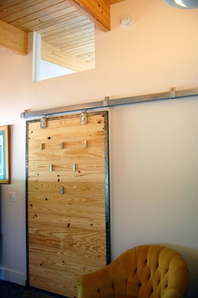 "To make the barn door for Myria's office, A.J. took leftover wood from the ceilings and crafted a sturdy sliding door. Then they took <a href=""http://www.ikea.com/us/en/catalog/categories/departments/bedroom/16274"">Bjarnum coat hooks</a> from <a href=""htt"