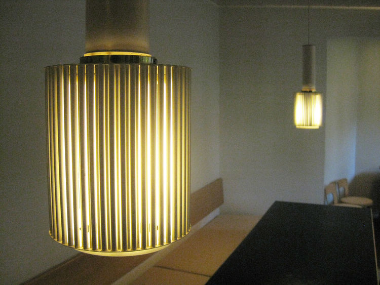 """Aalto would often linger for discussion-filled afternoons in the Atelier's canteen. The A111 fixture (a variation of the A110 with brass tubing) was developed for Artek. In the company's prosaic naming methods """"A"""" recognized that the design was by Alvar A"""