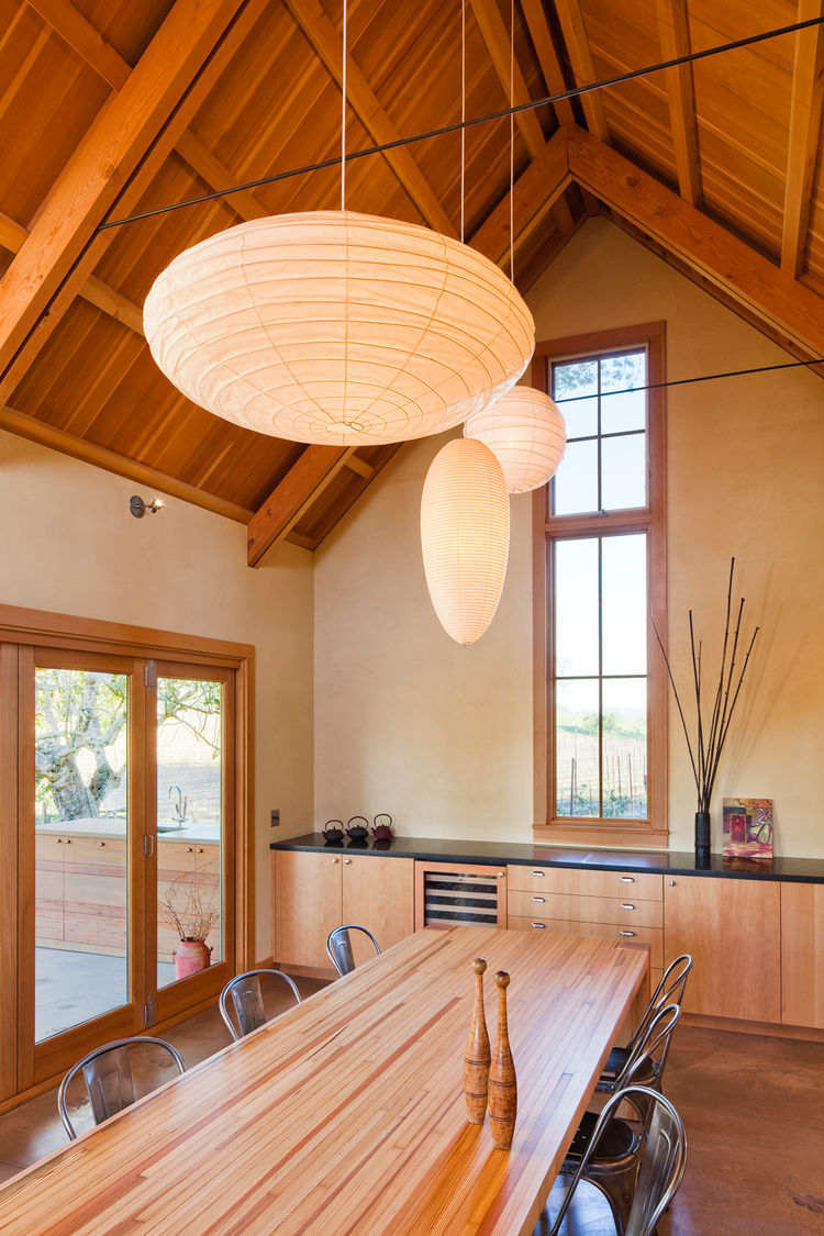 With exposed fir framing and clay plastered walls, the spacious dining room is the new social focus of the house. The custom dining table was created from salvaged bowling lanes. Connecting the home to the garden was a high priority, and a 14-foot-wide mu