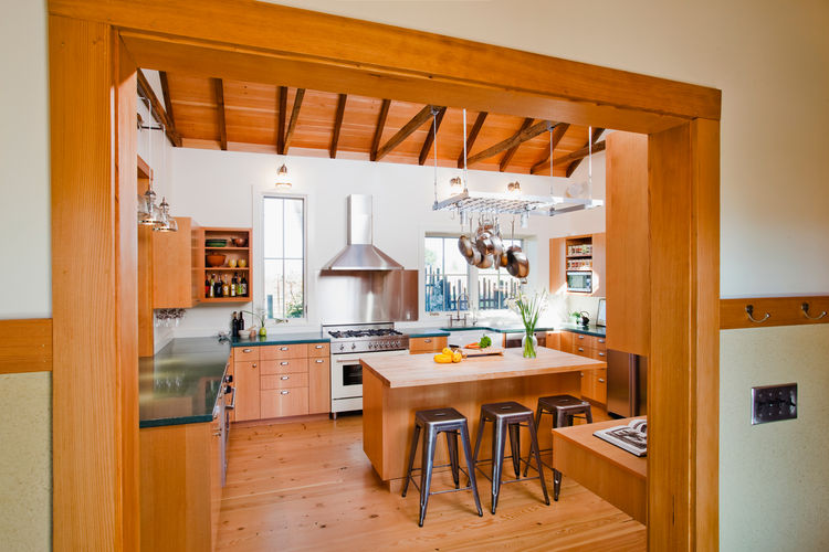 The new, open kitchen is the heart of the renovation, with views of the garden in every direction. The added kitchen and dining rooms feature ample south-facing windows along with carefully designed overhangs, awnings and porches that shade the high summe