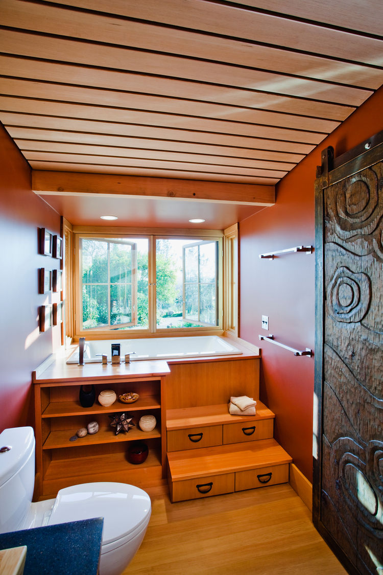 """The """"Zen-inspired"""" lower bathroom is designed with rich colors and textures. Local craftsmen were engaged for the """"tansu"""" tub (which overlooks the garden) and the carved bathroom door. Salvaged vertical grain Douglas Fir """"stadium select""""-grade bleacher se"""