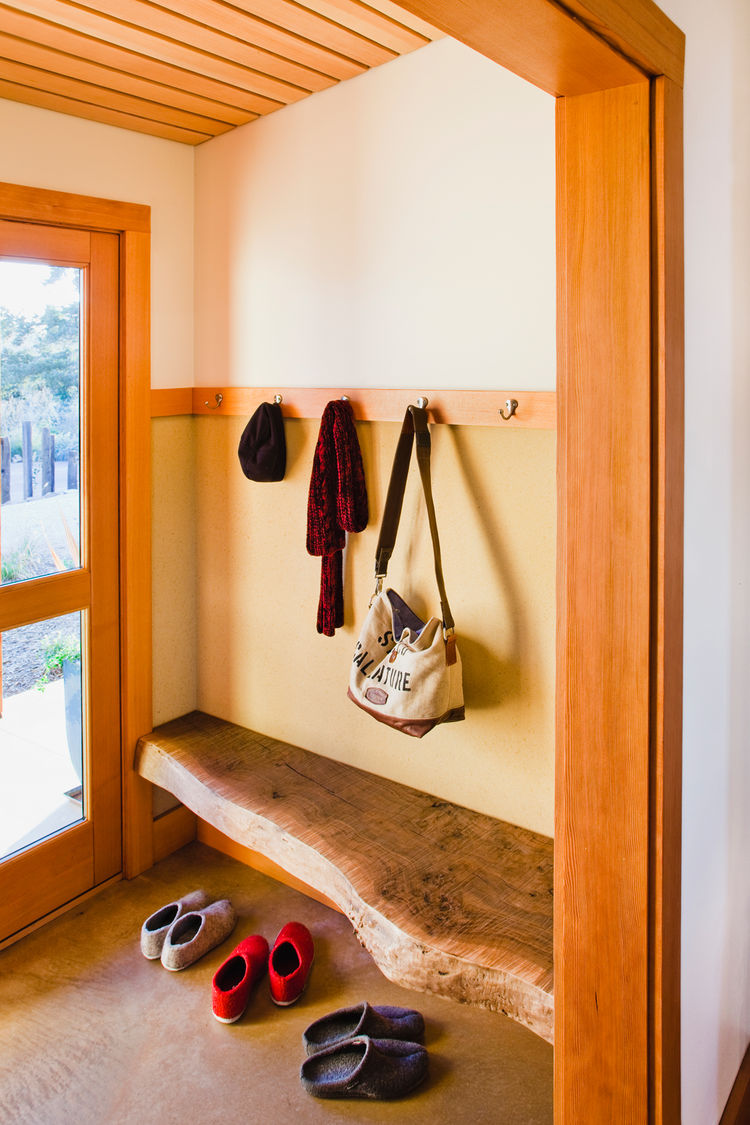 A live edge bench, harvested from the site, balances the carved door of the bathroom on the opposite end of the entry/mudroom.