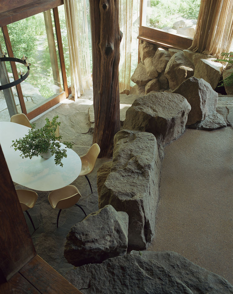 Organic architecture at its best: The sunken dining room features boulders and a more than one-hundred-year-old tree trunk that acts as the main support for the southeast corner of the house.