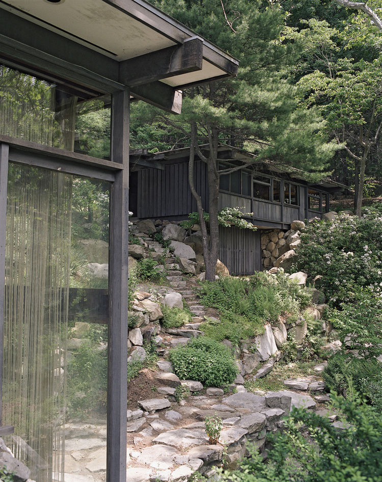 "On the land, which Wright dubbed Manitoga, he planted and cultivated native trees and wove stone paths around them. He diverted a river into an abandoned quarry, creating a pool that his daughter named Dragon Rock, as she ""likened the place where pool met"