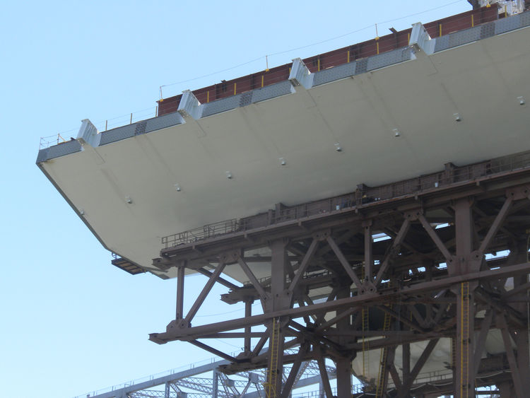 Because of the additional weight from the pedestrian and bike path on the southern side of the skyway and SAS bridge, counter balances (the small rectangles sticking out of the northern side of the bridge) had to be added to the spans.