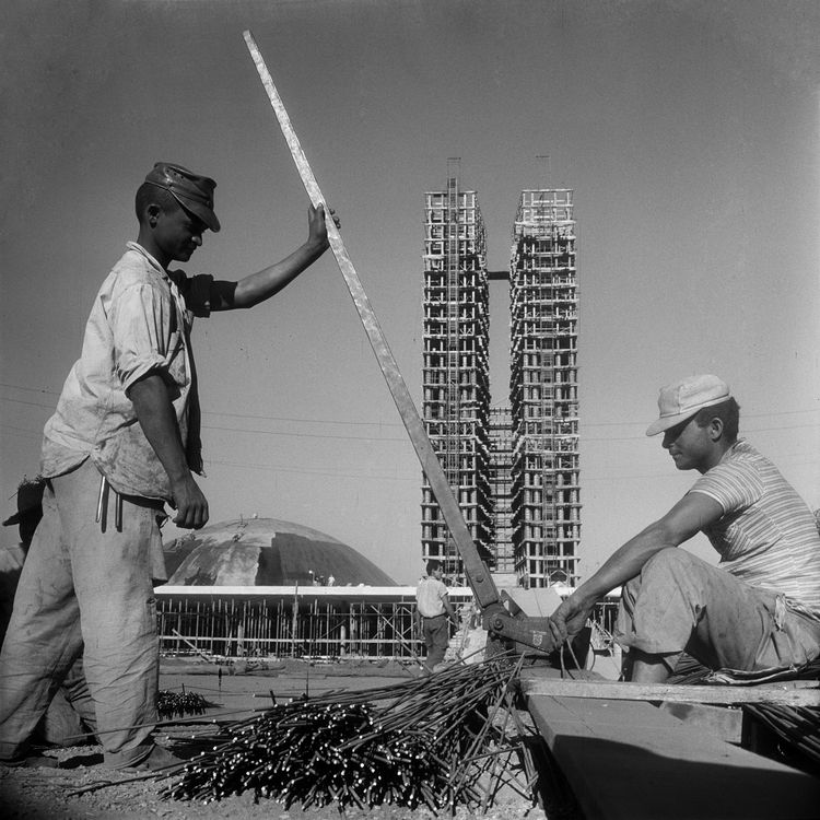 Workers continue constructing Brasilia with the scaffolding-clad towers of the National Congress in the background. Photo by Gervasio Batista.