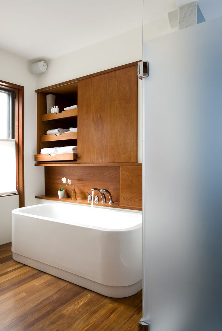 "The leftmost cabinet above the <a href=""http://www.duravit.com"">Duravit</a> bathtub (equipped with <a href=""http://www.kwcamerica.com"">KWC</a> fixtures) occupies the space where a doorway once lead into the living room, creating unnecessary traffic from t"