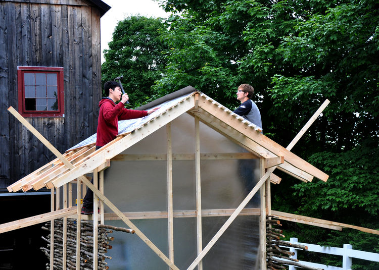 "Pictured here are two of the students at work on the Chicken Chapel. ""They were great,"" Moskow says. ""It'd be sunny in the morning then there'd be a rainstorm in the afternoon, but no one complained. It took really, really long days to finish it but they"