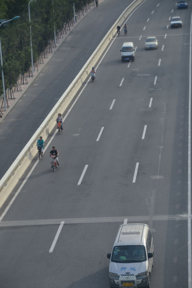 Pictured here, cars, bikes, and pedestrians sharing highway lanes in Tianjin.