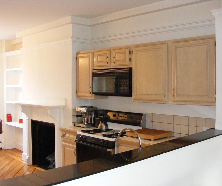 """Chris removed the existing cabinets, microwave, oven, and stove from the cutout in the kitchen and filled it in with <a href=""""http://www.ikea.com/us/en/"""">Ikea</a> cabinets to create a flush wall that runs nearly the entire length of the public space."""