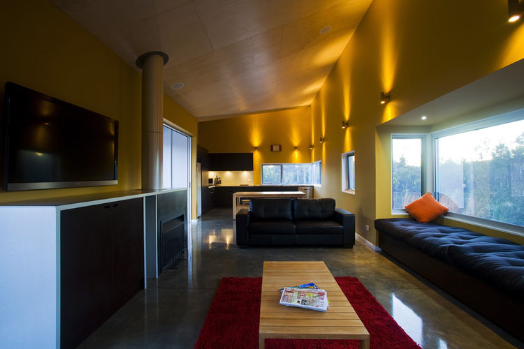 """The room extends into the main living area, illuminated by energy-saving LED lighting. At right is the """"popout"""" bay window, filled with banquette seating."""