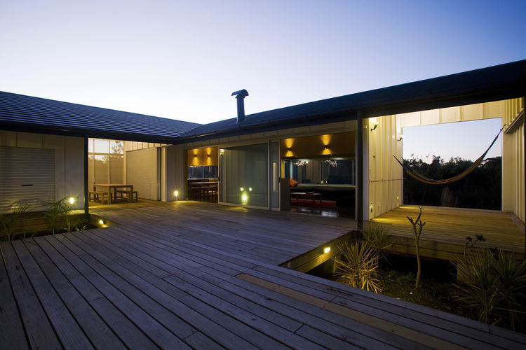 All rooms are accessible through the interior courtyard, which is raised several feet off the ground. Large sliders open to the living and dining areas; at right is one of two private hammock decks.