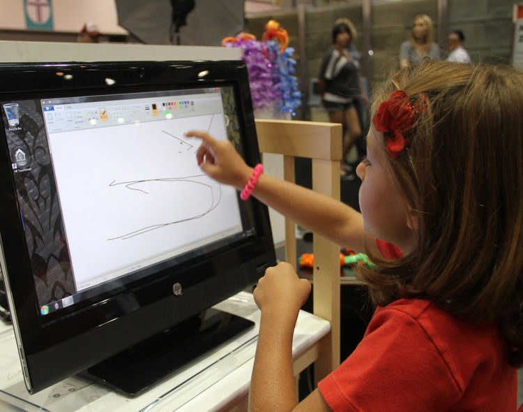 "A youngster tries out the <a href=""http://www.hp.com"">HP</a> Touchsmart technology, which allows kids to draw right onscreen."
