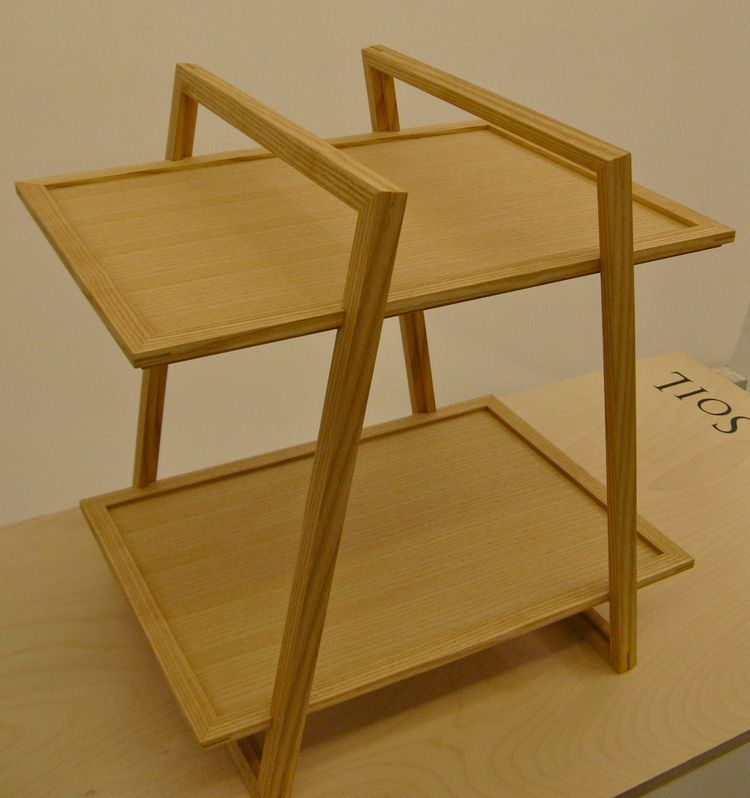 "Kengo Babata's white ash ""trame"" side table can also be used as two trays. The concept behind the Design Soil series—a collaboration with students at Kobe Design School, where Babata teaches—was to create ""souvenir furniture"" that could be carried on an a"