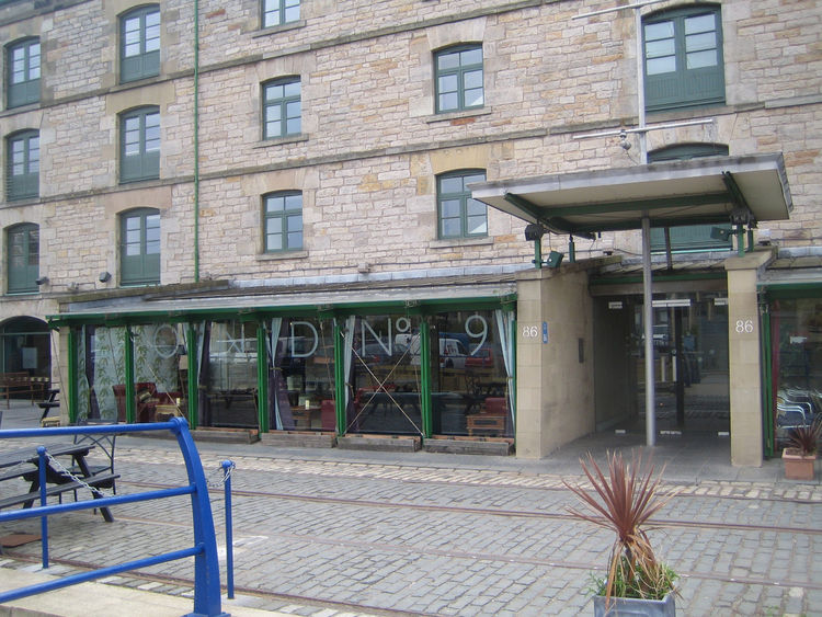 Here's a little strip in the Leith neighborhood called the Commercial Quay. In the last dozen years or so what was once a storage spot for whisky casks has been converted into a road of cafes. A nice little glass build-out with a uniformly green metal str