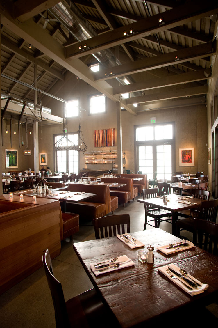 "The dining room is dominated by large tables and booths meant to emulate a farmhouse aesthetic. The designers looked locally and found lounge tables at <a href=""http://roostco.com/"">Roost</a> in Sausalito; communal tables and dining table tops from reclai"