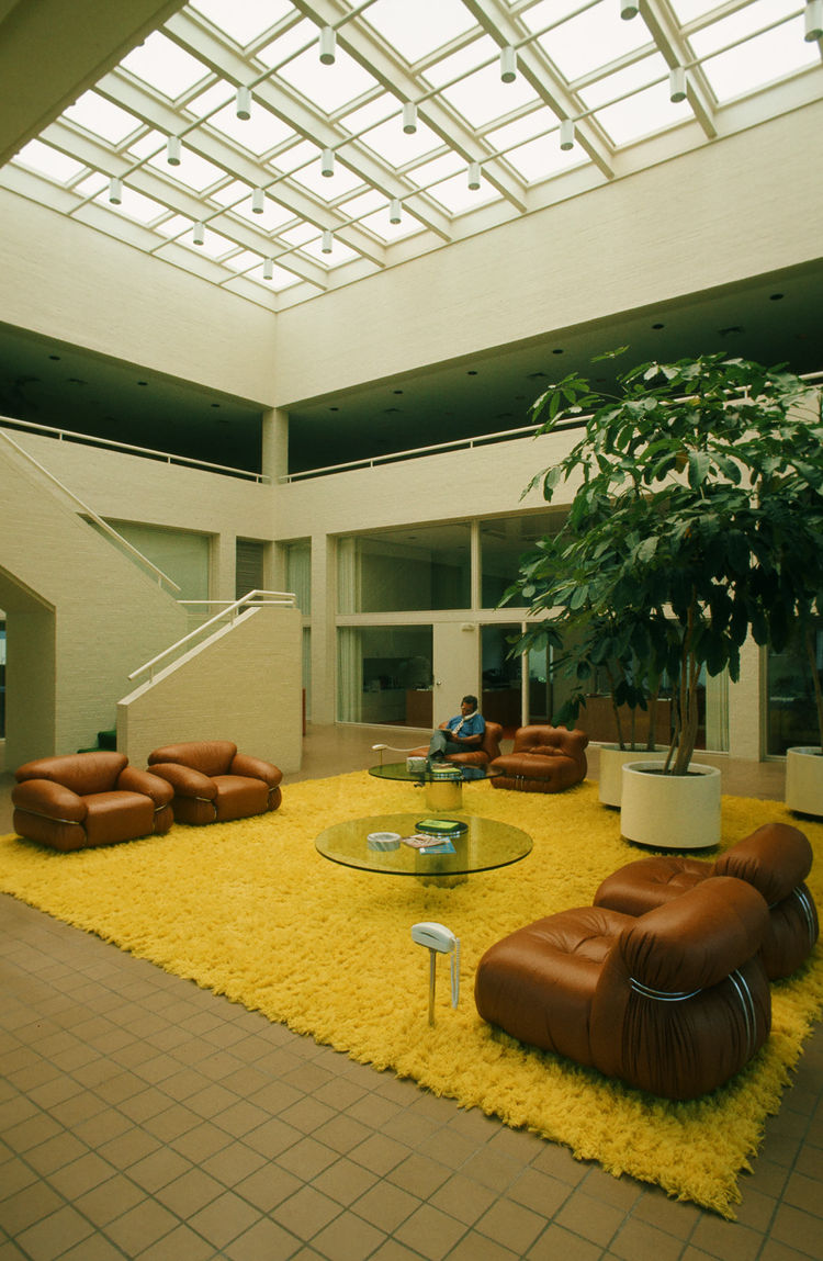 Once we move inside the Swink Agency to the lobby, we see that some very groovy action indeed. I love the telephone on the pedestal, the epic yellow rug, and the leather chairs by Tobia Scarpa for Cassina. They're Model 944 Soiranas from 1969. Also be sur