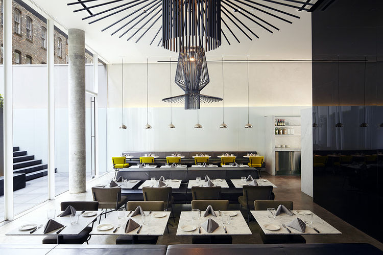 In the Americano restaurant, the walls—one in reflective black, the other in white lacquered glass—create a striking backdrop for the marble tables, yellow felt and khaki cloth chairs, and black leather banquettes that line the space. The large suspended