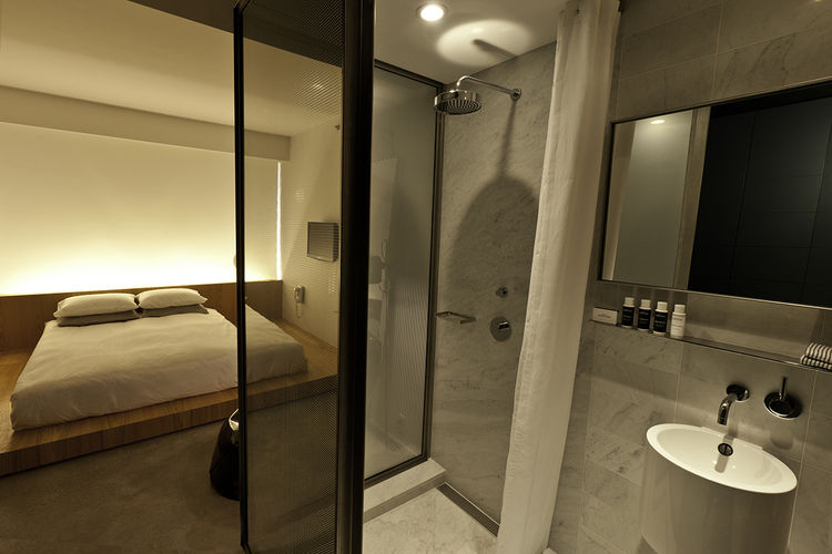 The shower stalls are enclosed in glass and perforated chrome sheet metal, reminiscent of the hotel's exterior. The bathrooms are outfitted in tumbled Carrara marble, as well as Dornbracht sink fixtures, shelves and mirrors.
