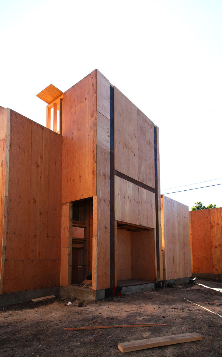 This tall structure holds an external staircase leading up to a rooftop garden and media studio. The square opening underneath will house an outdoor fireplace by Spark Modern Fires. The tall opening left of that is a storage cabinet.