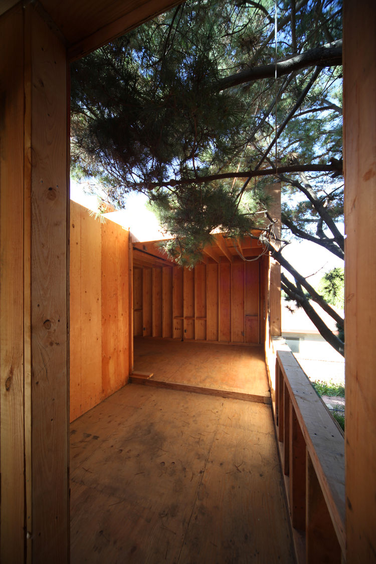 An outdoor deck connects the two guest bedrooms while Monterey pine branches poke into the deck space.