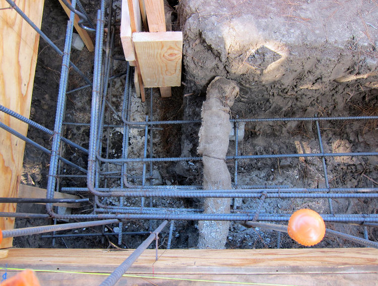 Rebar is placed in the trenches in locations as specified by our structural engineer. A tree root is shown wrapped in packed mud and wet burlap cloth.
