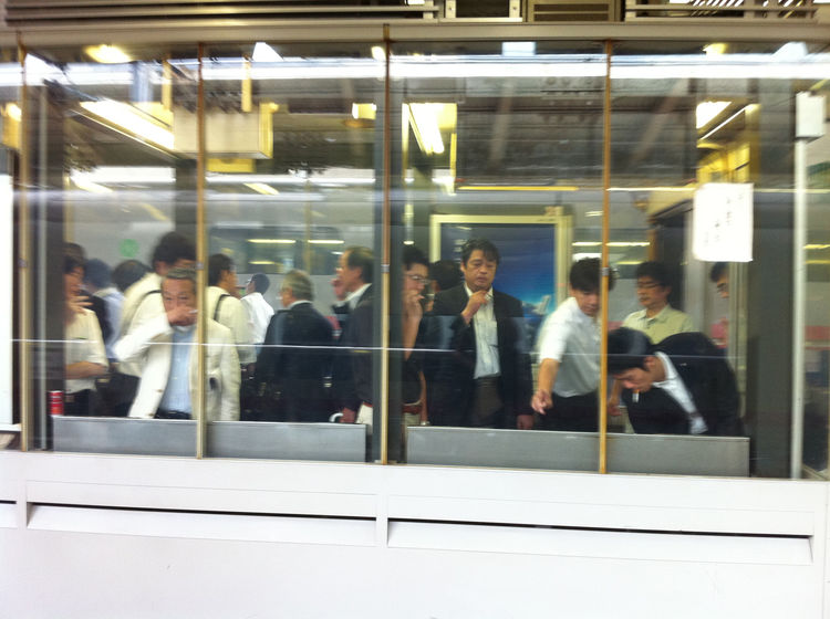 """A glassed-in smoking cabin at a Japanese train station. Katayama writes, """"it has this wonderful zoo animal on display effect that I found deeply entertaining as I waited for the shinkansen to Sendai a few weeks ago."""