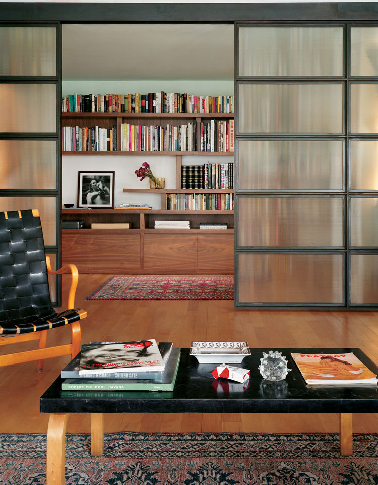 """Jaklitsch's Svensson Loft in New York is a mid-century design fan's fantasy of ample light and lovely wood. A generous library (behind the paneled doors) can be closed off completely from the rest of the house. Photograph by <a href=""""http://www.warcholpho"""
