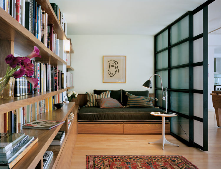 """Inside the library is a wall of books and spots to lounge. Photograph by <a href=""""http://www.warcholphotography.com/"""">Paul Warchol</a>."""