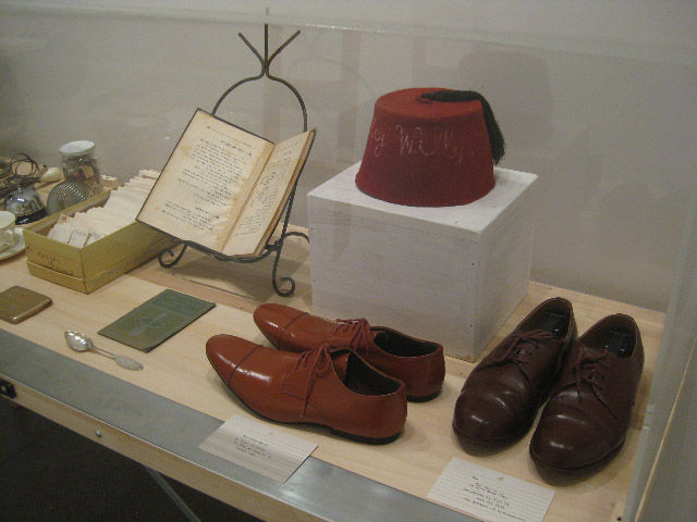 """Here's another view of that vitrine with Kalman's ephemera. She told me that she wore the brown shoes, which are too big for her, """"in the hope of slowing down time."""" She then mimed slow, massive steps for me as we continued around the gallery. Maira Kalma"""