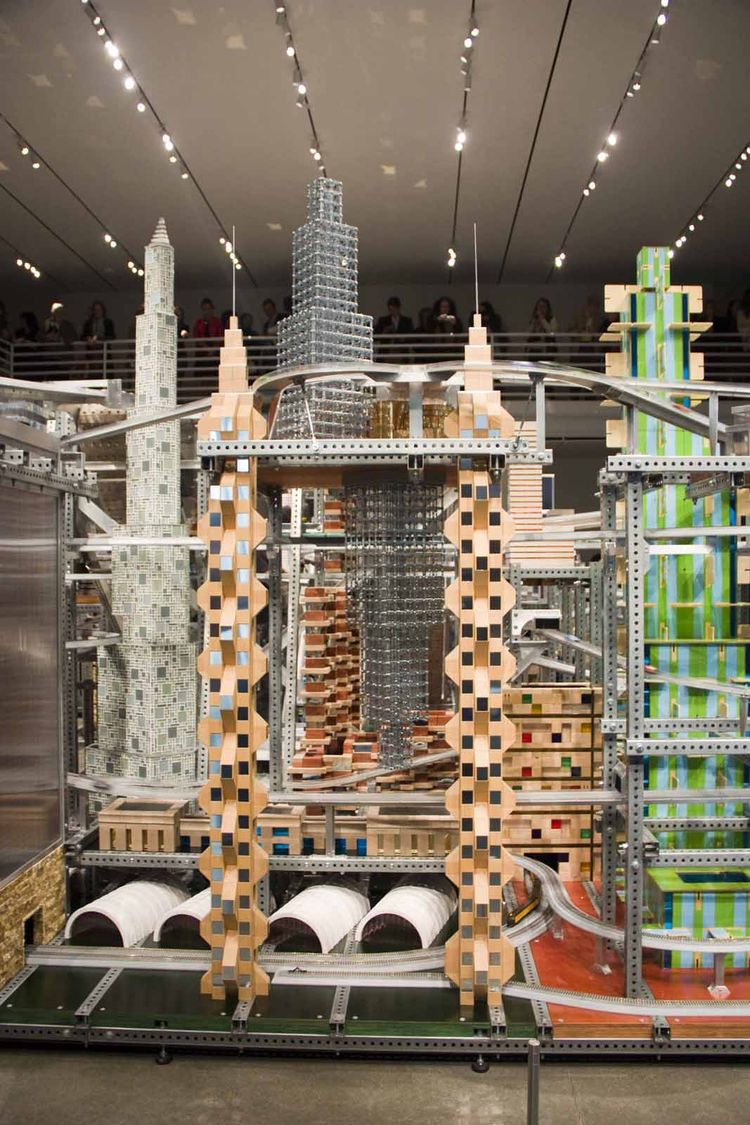 """Burden did not specifically model any of the buildings to existing structures in the real world. """"We just make mock-ups out of cardboard, make big piles of them and decide which one to use,"""" says the artist."""