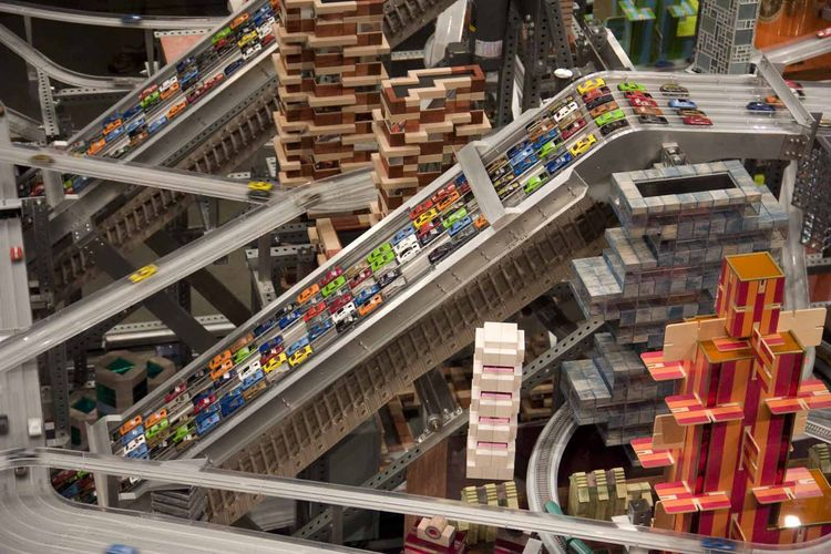The frenzy of cars runs on gravity, save for three conveyor belts set right in the middle of the exhibition. Magnets on the conveyor belts attract the magnets inside the cars and help pull them up a steep incline, where they are released down into the int