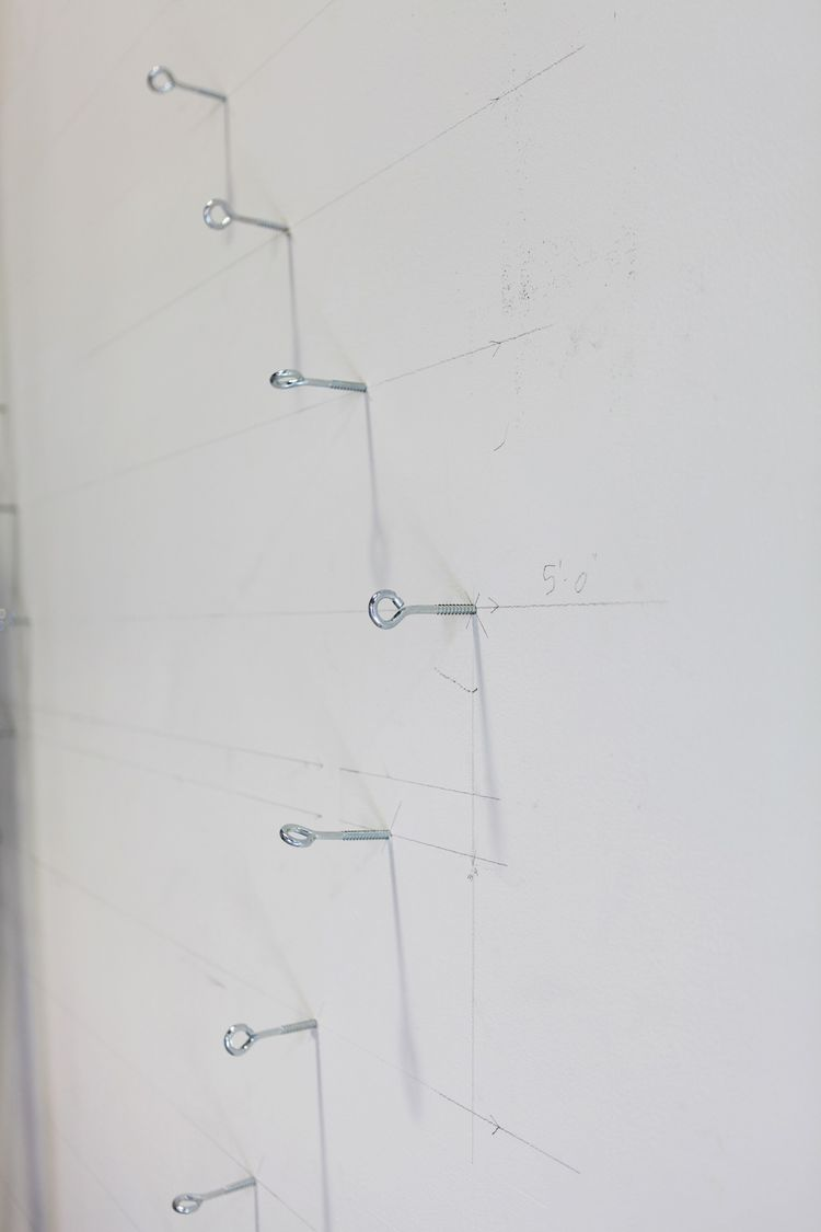 First step of the installation: embed the wall with eye hooks, which will anchor the stainless steel wire that will crisscross through the gallery, from floor to ceiling.