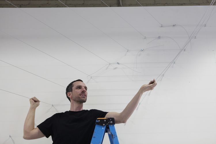 Cy Keener checks to see how tightly strung the stainless steel wire in the gallery has been hung.