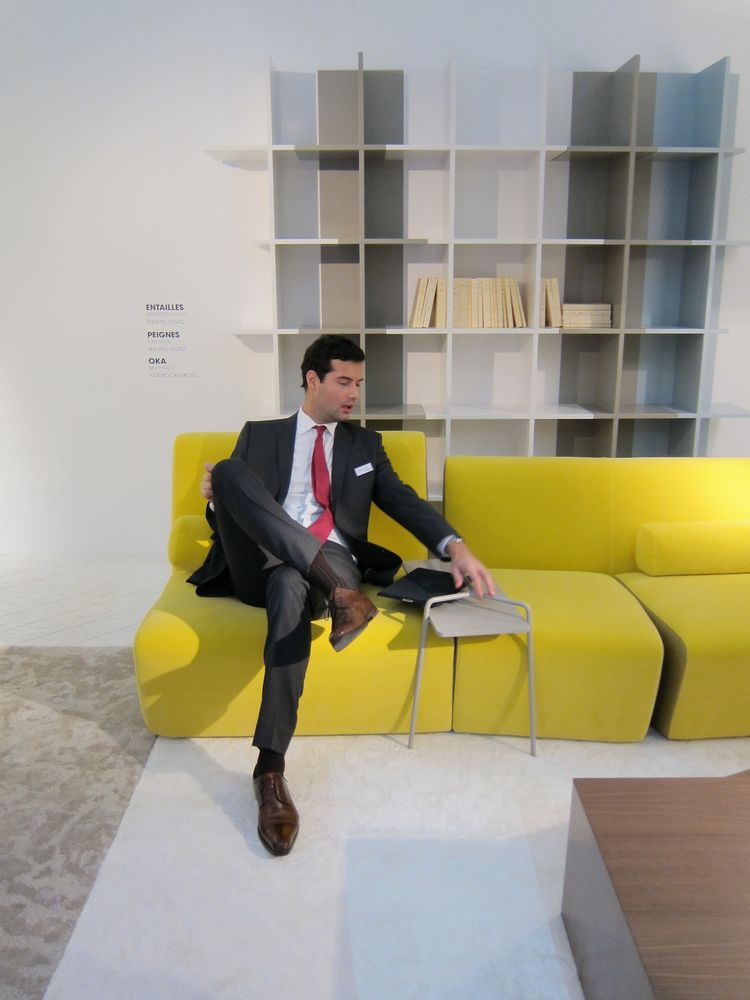 Roset demonstrating how the Philippe Nigro side table that straddles the Entailles couch is the perfect place to rest his iPad. Behind him is the Oka bookcase, which comes in three sizes that nestle together seamlessly to accommodate any book collection o