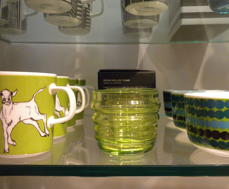 Displayed between a mug featuring Miina Äkkijyrkkä's Iltavilli design with a young calf and a bowl with Maija Louekari's colorful Räsymatto pattern is Anu Penttinen's Sukat Makkaralla glasses, designed in 2010 and available in a range of colors.