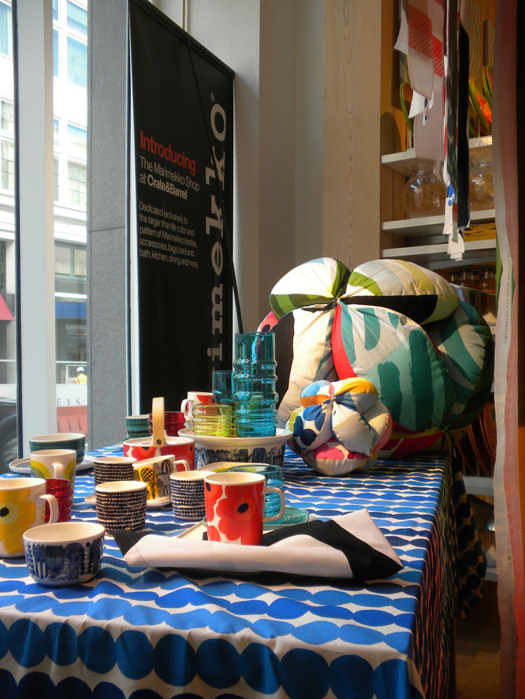 This tabletop display features mugs with Marimekko's iconic Unikko pattern designed by Maija Isola in 1964 as well ceramics with Maija Louekari's black dots Räsymatto design and her blue-on-white Siirtolapuutarha pattern, among others.