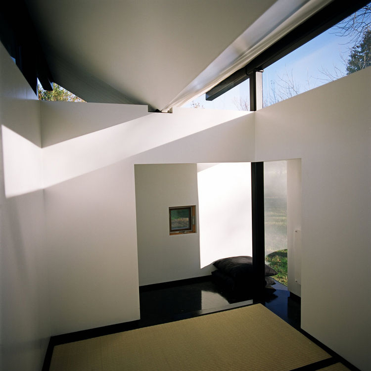 "Inside, a large window opposite the main door frames a view of mature trees. The main interior spaces is the raised platform supporting three tatami mats. ""The floor of glossy ebonized birch has the sensation of a deep, still pond,"" Poss says. ""The grass"